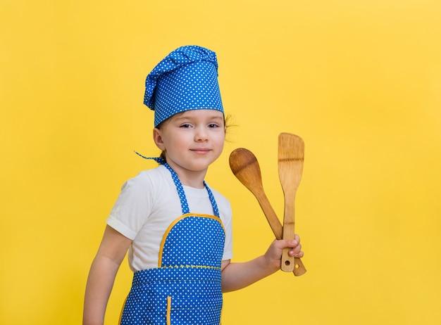 Маленькая девочка играет в повара. милая девушка в костюме повара с деревянной лопаточкой и ложкой. маленькая девочка в фартуке и синей кепке в горошек.