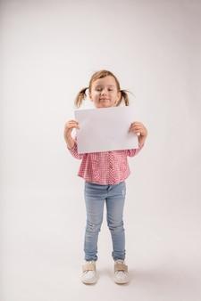 白いスペースに三つ編みのかわいい女の子は、コピースペースの白いシートを保持しています。格子縞のシャツとジーンズを着た小さな女の子が広告で葉っぱを持っています。