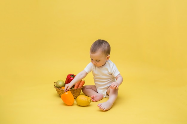 黄色のスペースに野菜と果物の枝編み細工品バスケットを持つ男の子。少年は白いボディースーツに座って、レモンとピーマンで遊んでいます。