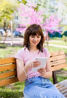 Молодая девушка сидит на скамейке с планшетом в наушниках в парке. милая девушка в розовом топе смотрит на свой планшет. дистанционное обучение.