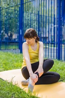 Молодая девушка сидит на ковре и морщится от боли. девушка сидит на желтой циновке на траве и потирает больную ногу.