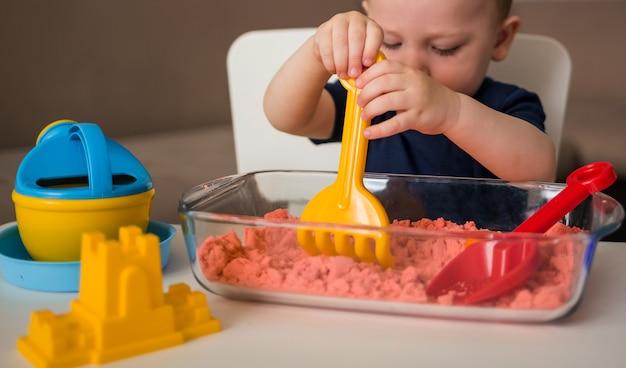 Желтая лопатка крупным планом. развивающие игры для детей с кинетическим песком. набор для песочницы.