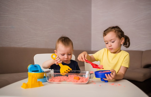 Младший брат и сестра играют в комнате с кинетическим песком. дети делают фигуры из песка.