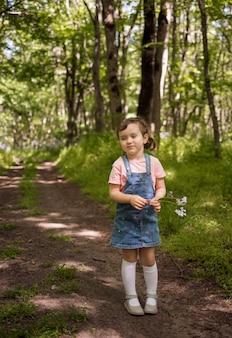 Красивая маленькая девочка в джинсовом сарафане гуляет по летнему лесу.