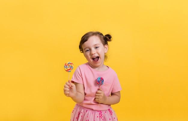 Смеющаяся маленькая девочка в розовой футболке с хвостиками держит два разноцветных леденца на палочке