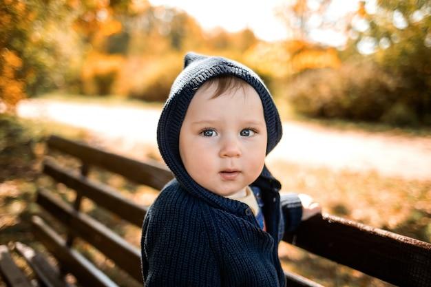 秋の公園でブルーのカーディガンの男の子。