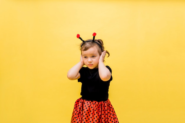 Красивая девушка в костюме божьей коровки прикрыла уши от желтого цвета