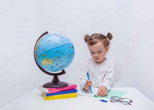 小さな女の子はノートとペンを分離した白の上で学習しています