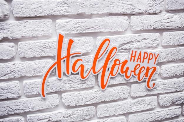 白い石の壁にオレンジの碑文「ハッピーハロウィン」