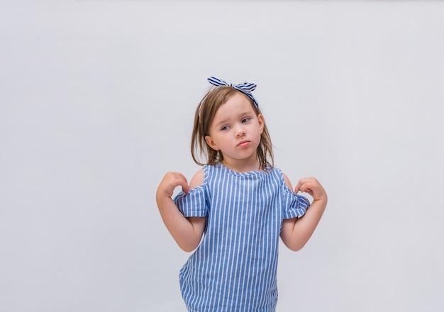 Расстроенная маленькая девочка в полосатой блузке на белом фоне