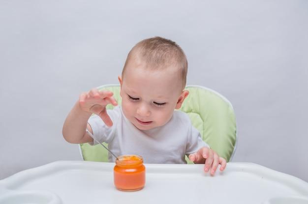 小さな男の子は分離された白のマッシュニンジンを食べるテーブルに座っています。