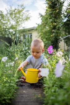 小さな男の子が黄色のじょうろで庭に座っています。