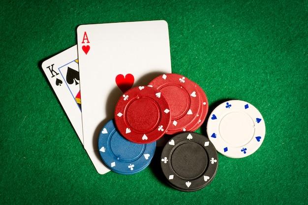 Покерный стол с черными игровыми фишками и двумя картами