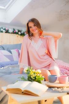 ベッドでリラックスした美しいブルネットの若い女性の肖像画