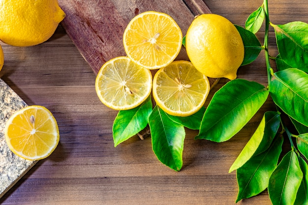 Вид сверху лимона и зеленых листьев на деревянный стол