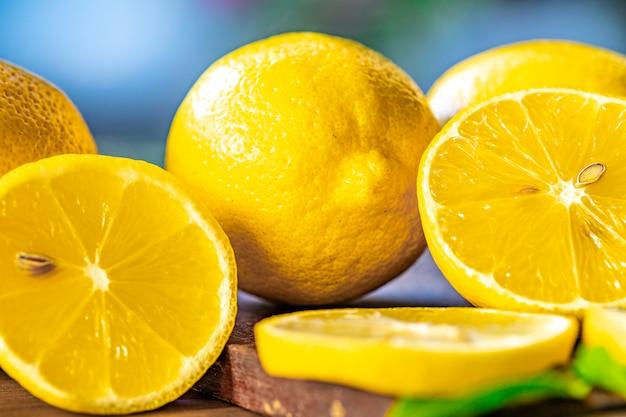 Крупным планом лимона и зеленых листьев на деревенский деревянный столик