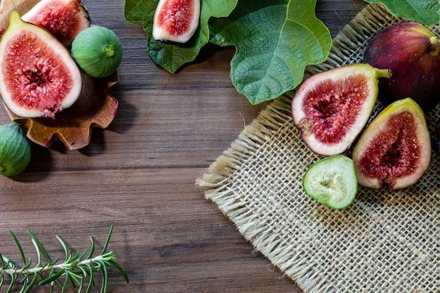 木製のテーブルに緑の葉とイチジク