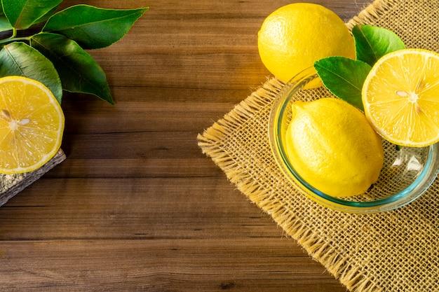 素朴な木製のテーブルにレモンと緑の葉が付いているボールのクローズアップ
