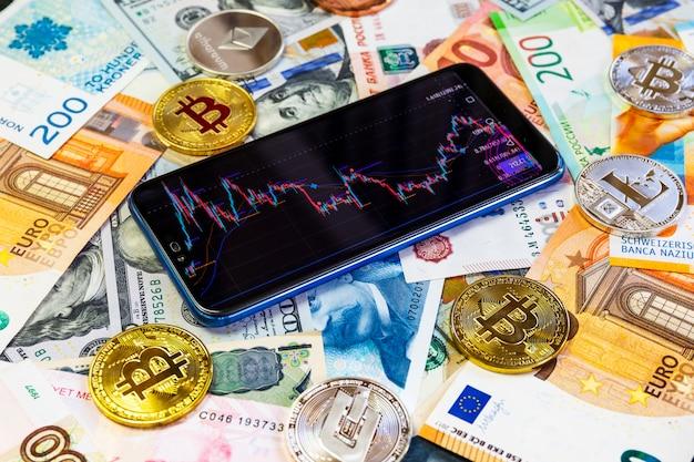 Различные криптовалюты и смартфон с графиком.