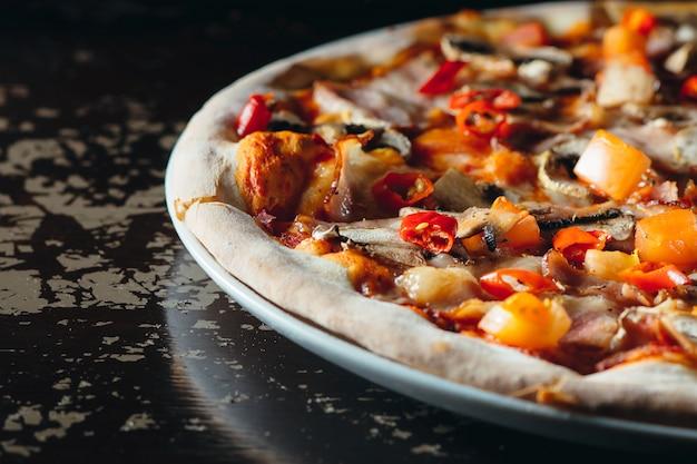 茶色のテーブルに溶けたチーズ、トマト、唐辛子、マッシュルーム、ハーブとイタリアのピザを閉じます。おいしいピザ。