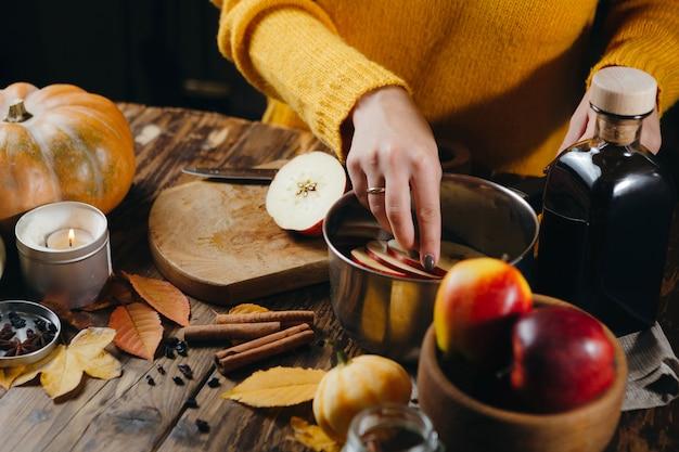 熱いワインを作るための鍋に刈り取らりんごを入れて黄色いセーターの女性の平面図です。