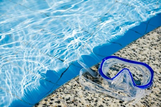 青い水でプールの近くの青いマスクを泳いでいます。