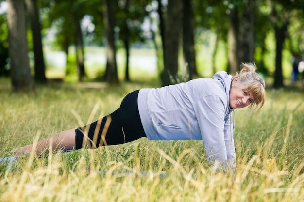 公園でヨガをしている年配の女性