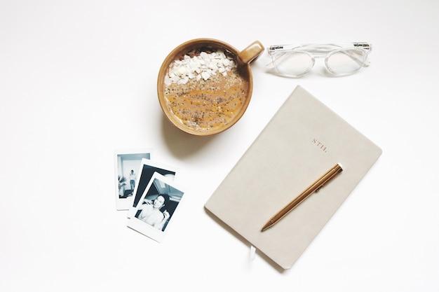 ノートとペンの横にある茶色のセラミックカップ