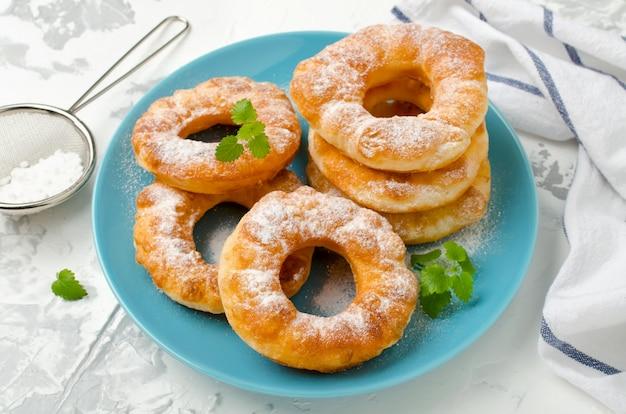 Домашние жареные ванильные пончики на белом фоне