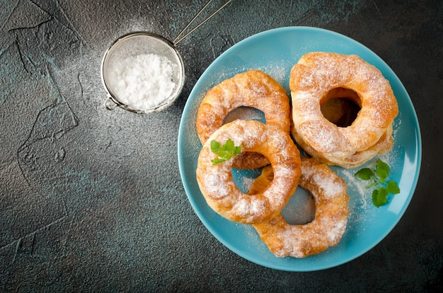 Домашние жареные пончики с ванильным творогом на темном бетонном фоне