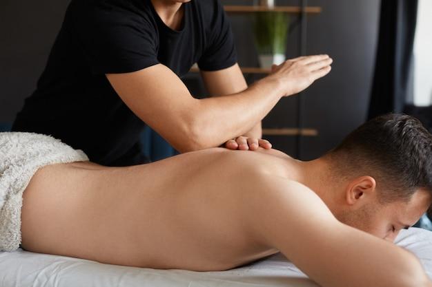 スパで背中と肩のマッサージを楽しんでいる若い男。プロのマッサージセラピストがアパートで男性患者を治療しています。リラクゼーション、美容、ボディ、顔の治療コンセプト。ホームマッサージ