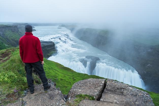 Турист смотрит на водопад гульфосс в исландии
