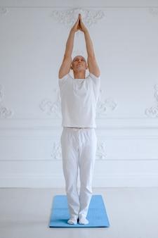 白い壁に高度なヨガの練習の男