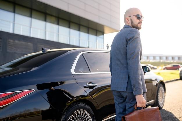 Бизнесмен ходит на фоне здания и машины