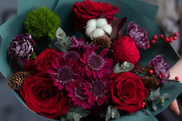 手にクローズアップの花。花屋の職場。バラ、菊、カーネーション、その他の花で花束をアレンジする女性。