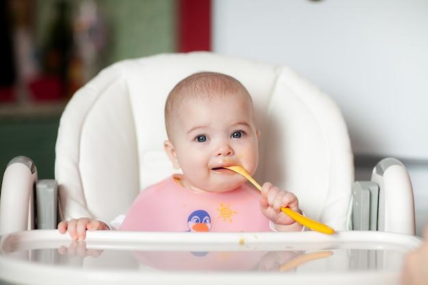 元気な赤ちゃんは、スプーンで食べ物そのものを食べます。高い椅子で幸せな子供の女の子の肖像画。