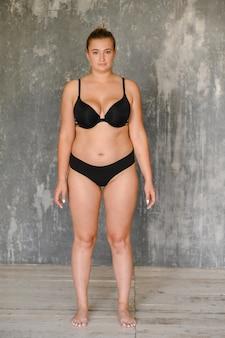 壁近くに水着姿の豊満少女が立っている。ボディポジティブ。サイズプラス