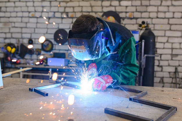 強い男は溶接マスクの溶接工と革の溶接工、金属製品はガレージの溶接機で溶接され、青い火花が側面に飛ぶ