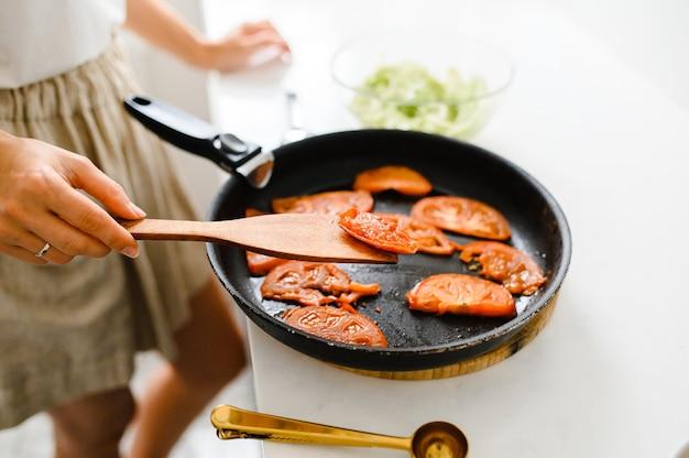 Жареные помидоры на сковороде. вишня