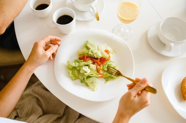 Девочка ест салат из помидоров и овощей