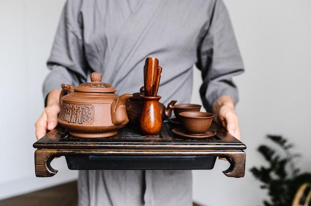 Мужчина держит поднос с набором для китайской чайной церемонии