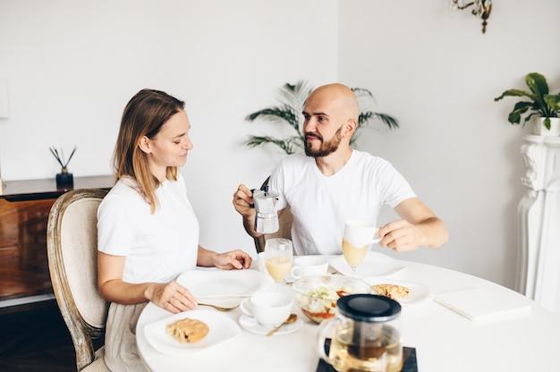 一緒に家で朝食を持っている若い幸せなカップル。