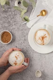 コーヒーと白いセラミックのマグカップを持っている人