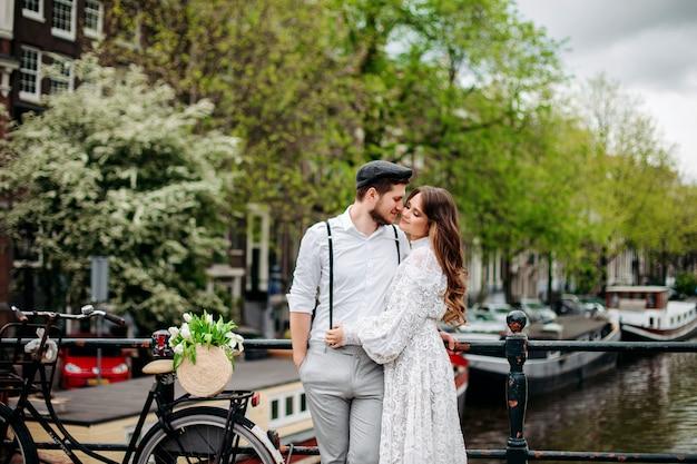 美しい男と女は抱擁し、旧市街の背景にキスします。