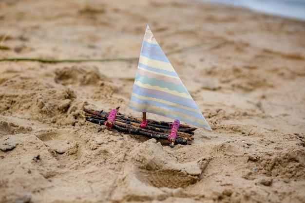 Одна игрушечная лодка на песчаном пляже. игрушечный парусник в реке.