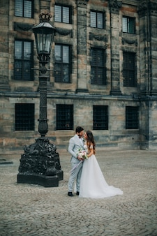 美しい花嫁と花婿を受け入れ、屋外での結婚式の日にキス