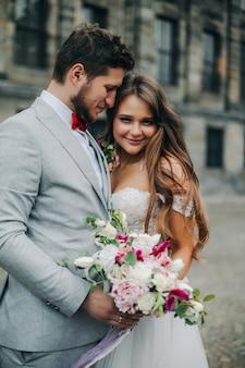 結婚式。スーツを着た新郎と白いドレスを着た花嫁が並べてブーケを持っている