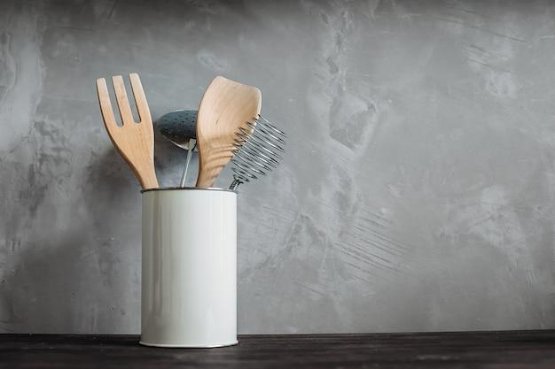 Кухонные инструменты, деревянные столовые приборы и металл в керамическом горшке против серой мраморной стены текстуры.