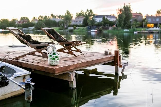 Деревянный шезлонг на скамье подсудимых на берегу озера