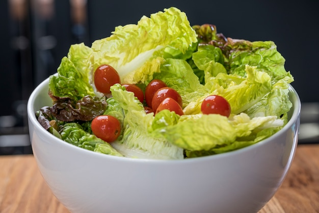 Салат из салата и помидоры черри в белой миске на деревянном столе